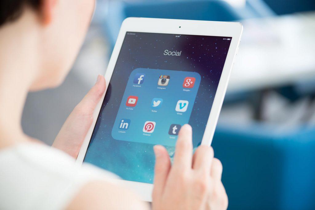 Mulher olhando para tablet procurando soluções para o seu jornal regional