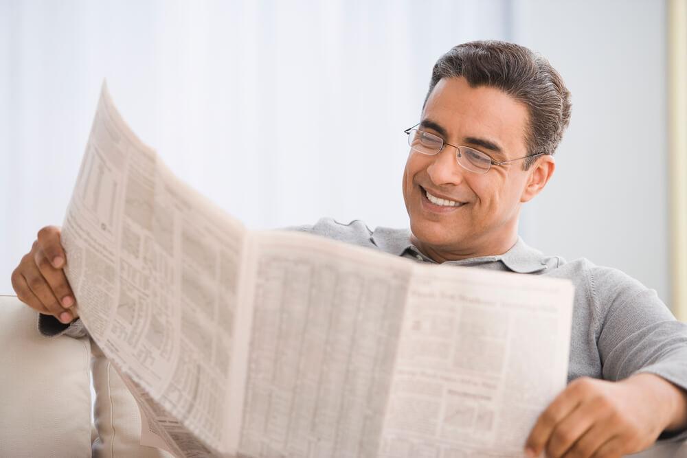 Pessoa lendo jornal impresso