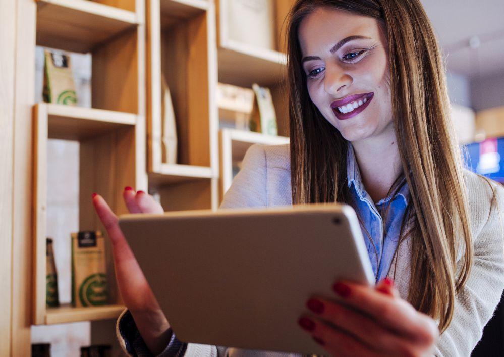 Mulher olhando jornal impresso no tablet